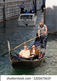 09/10/2018 Venice, Italy. Gondolier with two tourists in to the gondola. Enjoy the view.