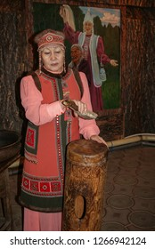 09.12.2008, Yakutsk, Russia. An elderly woman in national costume conducts a tour of the museum and talks about the authentic musical instrument of the Yakut people.