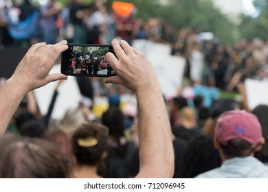09/17 Central Park, New York City. A protestor uses a mobile phone to take a picture of the speakers at the DACA march.