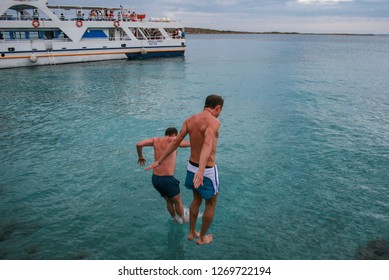 09.20.2008, Hersonissos, Crete, Greece. A young men jumping into water on background of the ship.