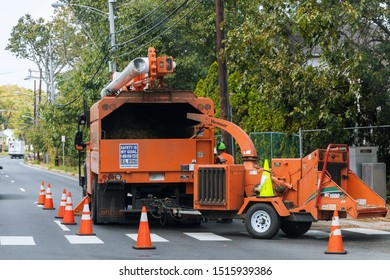 09.27.2019 Lakewood NJ USA. A tree chipper or wood chipper is a portable machine used for reducing wood into smaller wood chips blowing tree branches cut up into the back of a truck. Storm damage tree