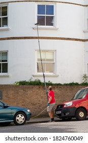 09/29/2020 Portsmouth, Hampshire, UK A window cleaner using a telescopic brush to clean windows that are at a height