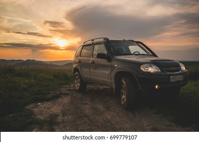 1 august 2017.Dusty SUV Chevrolet Niva on the background of beautiful sunset and mountains. Russia, Republic of Altai