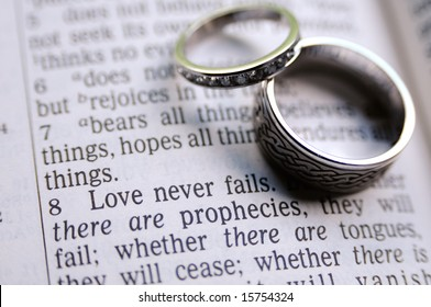 1 Corinthians 13:8 verse with two hand-crafted wedding rings in frame as well