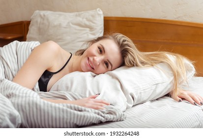 1 cute white girl lying in bed and smiling
