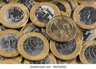 1 dollar coins in the middle of several 1 real coins on a wooden table
