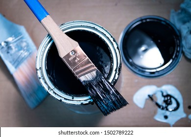 1 inch paintbrush resting on open can of enamel paint