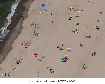 1 June 2019, Monster, Holland. Aerial view of a crowded sandy beach at the dutch coastline and North Sea near Monster West Beach. A lot of people and colorful parasols and towels.