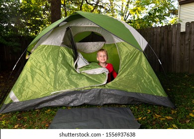 1 Little Boy Plays Alone in His Backyard Inside of a Green Camping Tent