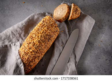 1 loaf of fresh grain bread, slices, knife on a gray towel on a gray background close-up, food, top view
