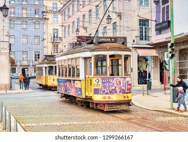 1 March 2018: Lisbon, Portugal - Tourists favourite tram 28 in Figueira Square, mother pointing it out to child.