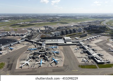 1 May 2016, Hoofddorp, Netherlands. Aerial view of the F-gate at Schiphol Amsterdam Airport with planes from Qatar and KLM. In the back the arrival hall and the tower.
