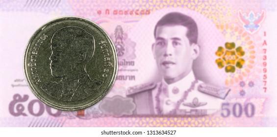 1 new thai baht coin against 500 new thai baht banknote