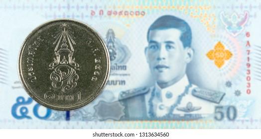 1 new thai baht coin against 50 new thai baht banknote