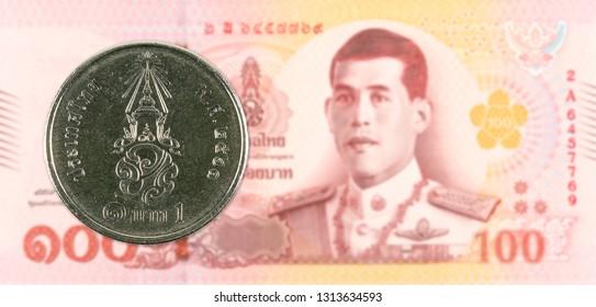 1 new thai baht coin against 100 new thai baht banknote