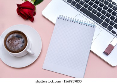 1 notebook with a clean sheet, laptop keyboard, a Cup of black coffee, red rose, pink lipstick on a beige background