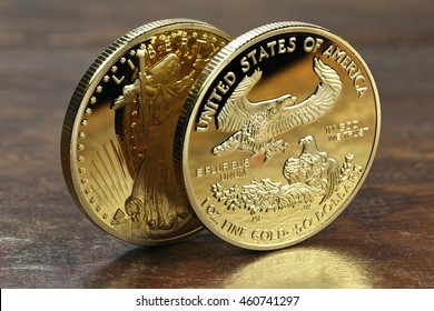 1 ounce American gold eagle bullion coins on wooden background