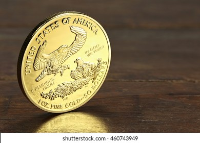 1 ounce American gold eagle bullion coin on wooden background