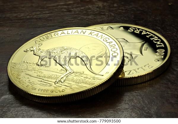 1 ounce Australian Kangaroo gold bullion coins on wooden background