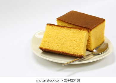 1 Pieces Cutted Homemade Castella Cake on White Ceramic Plate With Silver Dessert Spoon