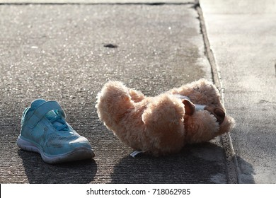 1 side of little girl shoe and her doll were left or fall off on the road.Nobody,girl was disappeared,only small blue shoe and doll are remain.Concept of  missing and exploited children,lose child