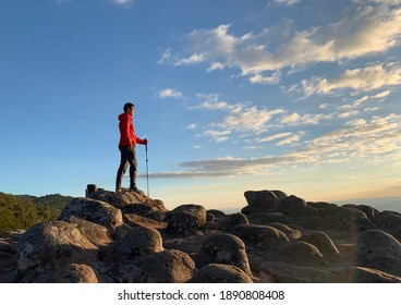 1 tourist standing on top of a rocky mountain  On the floor is a courtyard of buttons stone.  In the hand of the walking stick  It was the evening time when the golden sun flashed onto the ground.