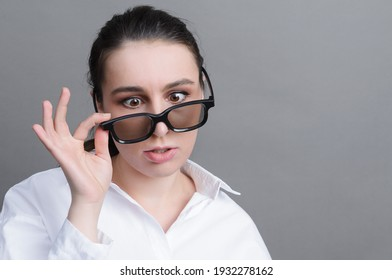 1 white young woman with glasses with a tired funny expression on a gray background close up