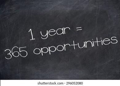 1 YEAR = 365 OPPORTUNITIES motivational quote written on blackboard.