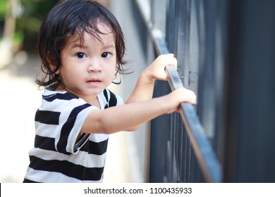 1 year and a half Asian boy grab the fence bar.Boy interest outside.Curious kids are able to look at the world around them and easily notice things that are interesting.Child improvement concept.