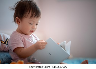 1 year old Asia baby girl reading book