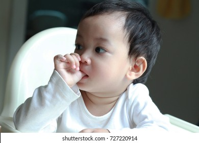 1 year old Asian toddler boy sucking his thumb or finger,comfort and entertain.Kid turns to the thumb when bored, tired, or upset.Children will give up the habit before they enter kindergarten.