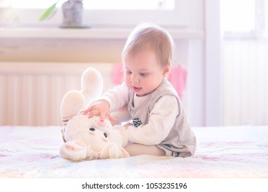 1 year old baby girl playing with a plush bunny