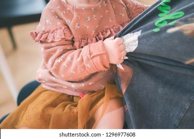 A 1 year old baby girl pulling her mother t-shirt close up picture