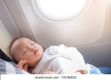 1 year old toddler baby boy child sleeping on Airplane with copy space,Toddler boy sleeping on mother's laps while traveling in airplane, Flying with children concept