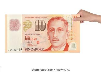 10 dollars Singapore money  in hand isolated white background.