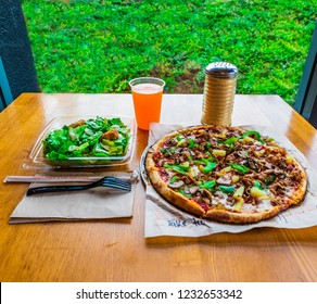 10 Inches Tasty Italian Pepperoni, Bell Pepper, Pineapple, Bacon Crumbs, Sausage, Onions  and Parmesan Cheese Pizza with Tossed Caesar Salad and Orange Drink on Table. Italian Cooked Food Restaurant