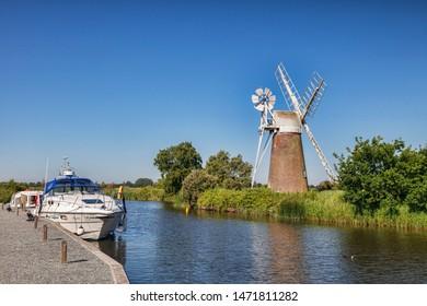 10 July 2015: Norfolk Broads, UK - Motor cruisers moored near Turf Fen Windmill on the Norfolk Broads, Norfolk, England