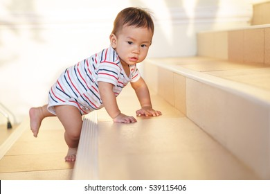 10 months adorable Asian baby development , climbing up stairs at home
