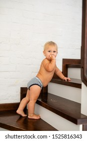 10 months adorable blonde baby development , climbing up stairs at home.