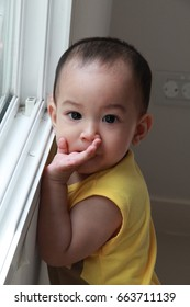 10 months Asian baby boy taking steps while holding on window gap and looking outside.