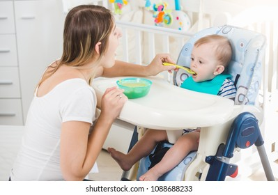 10 months old baby boy sitting in highchair and eatting porridge from spoon