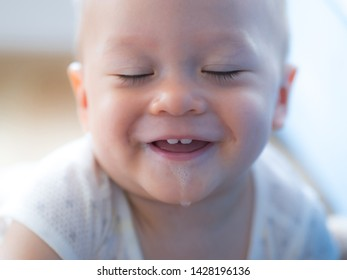 10 months old baby boy with funny face, drooling, happy playful bubbles saliva drool on child mouth, mixed race half Asian Thai, Polish European