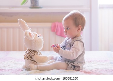 10 months old baby girl interacting with a plush toy
