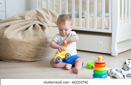 10 months old baby playing on floor with toy car and blocks