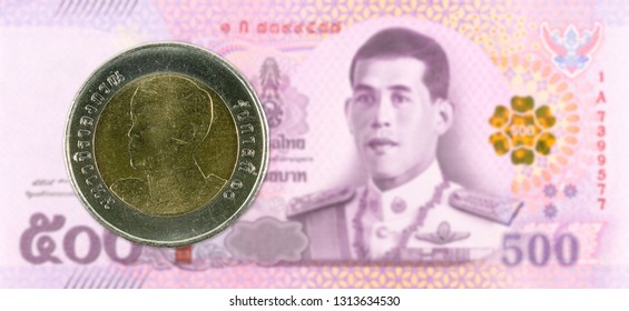 10 new thai baht coin against 500 new thai baht banknote