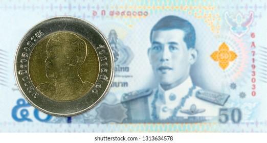 10 new thai baht coin against 50 new thai baht banknote