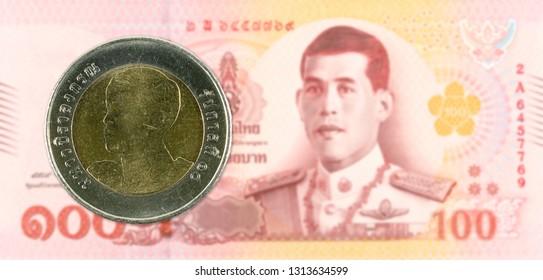 10 new thai baht coin against 100 new thai baht banknote