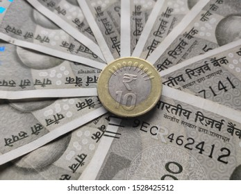10 rupee coin placed at center of circular distributed 500 indian rupees bank notes