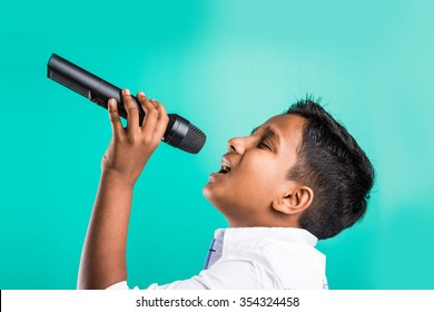 10 year old cute indian kid /boy in white shirt yelling or singing in microphone, isolated over green background