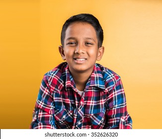10 year old happy Indian / asian boy isolated over yellow background